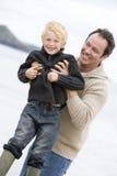 Padre che gioca con il figlio alla spiaggia immagini stock libere da diritti