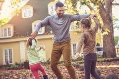 Padre che gioca con la figlia al cortile Fotografia Stock