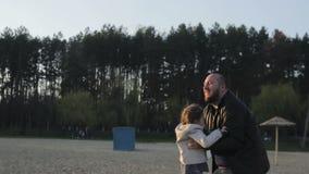 Padre che gioca con la ragazza della figlia che trowing nell'aria al tramonto sopra la riva del fiume archivi video