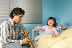 Padre che gioca sassofono per Bambino-Orizzontale Immagine Stock
