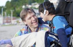Padre che gode della spiaggia con il figlio invalido Fotografie Stock Libere da Diritti