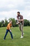 Padre che insegna al figlio felice che gioca volano all'aperto Fotografie Stock Libere da Diritti
