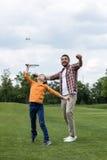 Padre che insegna al figlio felice che gioca volano all'aperto Fotografia Stock