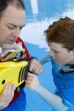 Padre che insegna al suo figlio ad usare le alette Fotografia Stock