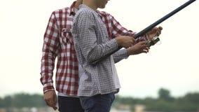 Padre che insegna a suo figlio adolescente a pescare, fondere canna da pesca ed utilizzare attrezzatura video d archivio