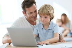 Padre che insegna a suo figlio che per mezzo del computer portatile Fotografia Stock Libera da Diritti