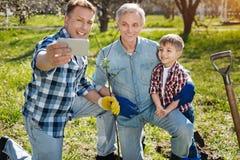 Padre che prende selfie con i membri della famiglia Fotografia Stock