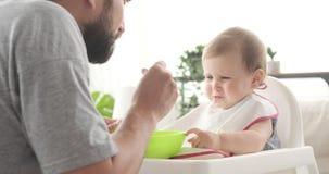 Padre che si alimenta gridando la figlia del bambino stock footage