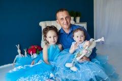 Padre che si siede con due figlie Immagini Stock