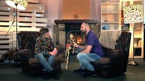 Padre che spiega suo figlio più anziano la struttura dell'osso della rappresentazione del corpo umano sullo scheletro archivi video