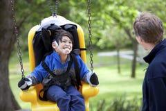 Padre che spinge figlio invalido sull'oscillazione di handicap Fotografia Stock Libera da Diritti