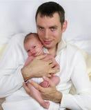 Padre che tiene piccolo un bambino anziano da quattro settimane. Immagini Stock