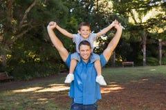 Padre che tiene suo figlio sulle spalle Immagine Stock