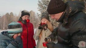 Padre che versa tè caldo dalla boccetta del termos per la famiglia alla passeggiata di inverno in foresta immagini stock libere da diritti