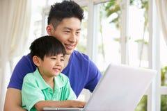 Padre chino e hijo que se sientan usando la computadora portátil fotos de archivo