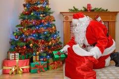 Padre Christmas che mette i regali sotto l'albero Fotografie Stock Libere da Diritti
