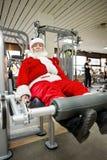 Padre Christmas que hace ejercicios en gimnasio Imagenes de archivo