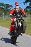 Padre Christmas que hace un wheelie Imagen de archivo