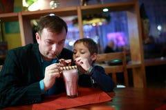 Padre con batido de leche de consumición del hijo foto de archivo