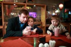 Padre con dos hijos que beben el batido de leche fotografía de archivo libre de regalías