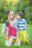 Padre con due bambini, mangianti le ciliege Immagini Stock