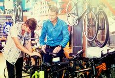 Padre con el adolescente que intenta la nueva bicicleta Imágenes de archivo libres de regalías