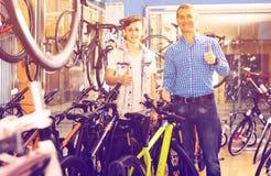 Padre con el hijo adolescente en tienda de la bici Fotografía de archivo libre de regalías
