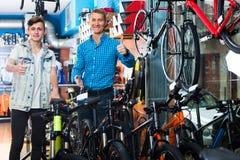 Padre con el hijo adolescente en tienda de la bici Imagen de archivo libre de regalías
