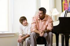 Padre con el hijo adolescente que se sienta junto en el país Imagenes de archivo
