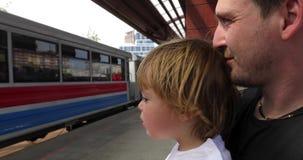 Padre con el hijo en la plataforma ferroviaria en día de verano almacen de video