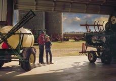 Padre con el hijo fuera del granero