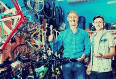 Padre con el hijo que elige la bici en tienda Imágenes de archivo libres de regalías
