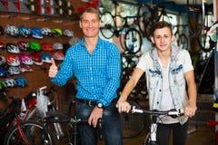 Padre con el hijo que elige la bici en tienda Fotos de archivo