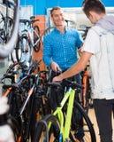 Padre con el hijo que elige la bici en tienda Foto de archivo