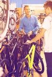 Padre con el hijo que elige la bici en tienda Imagenes de archivo