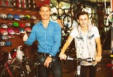 Padre con el hijo que elige la bici en tienda Fotografía de archivo libre de regalías