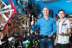 Padre con el hijo que elige la bici en tienda Fotografía de archivo