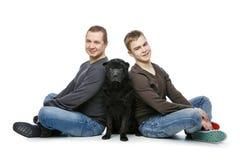Padre con el hijo que se sienta con el perro Imagenes de archivo