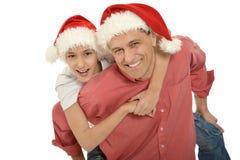 Padre con el niño pequeño en los sombreros de santa Fotografía de archivo libre de regalías