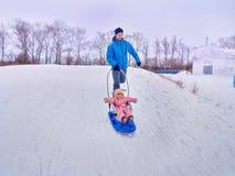 Padre con el paseo del niño en el invierno el trineo en nieve Fotos de archivo libres de regalías