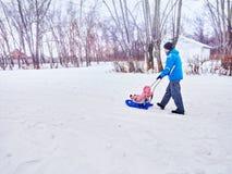 Padre con el paseo del niño en el invierno el trineo en nieve Imagen de archivo libre de regalías