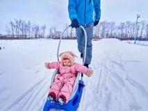 Padre con el paseo del niño en el invierno el trineo en nieve Imagenes de archivo
