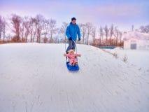 Padre con el paseo del niño en el invierno el trineo en nieve Fotos de archivo