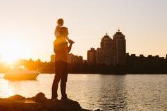 Padre con el pequeño niño en la puesta del sol Foto de archivo