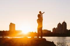 Padre con el pequeño niño en la puesta del sol Imágenes de archivo libres de regalías