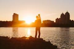 Padre con el pequeño niño en la puesta del sol Fotos de archivo