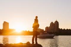 Padre con el pequeño niño en la puesta del sol Imagen de archivo libre de regalías