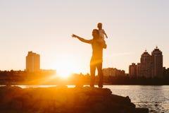 Padre con el pequeño niño en la puesta del sol Fotos de archivo libres de regalías