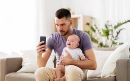 Padre con gridare bambino e smartphone a casa fotografia stock libera da diritti