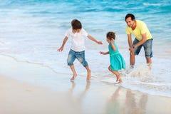 Padre con i bambini alla spiaggia Immagini Stock